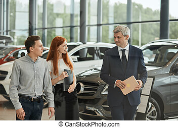 Car Business, Car Dealership, Customers and Rep Concept. Mature salesman talking to a young couple at the dealership showroom.
