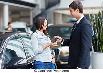Car sales - Seller gives keys to car girl in the salon