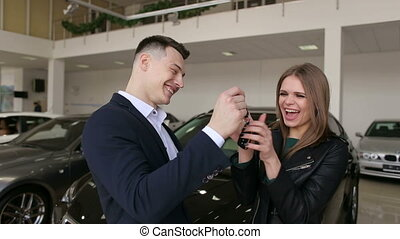 Car salesman gives a young happy excited girl the keys to a new car.