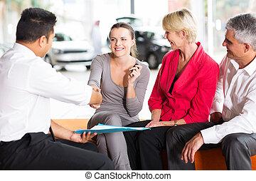 car salesman handshaking with young buyer