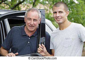 car salesman standing next to client