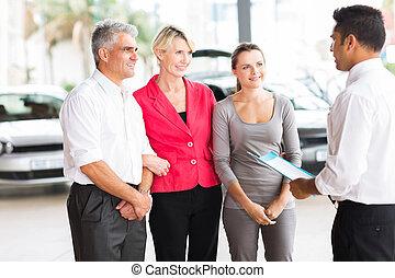 car salesman talking to family