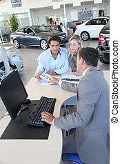 Car seller and couple looking at catalogue