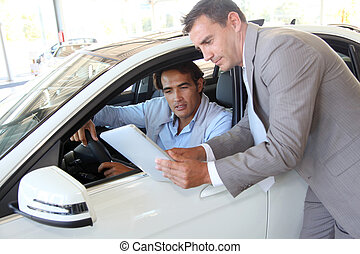Car seller with car buyer looking at electronic tablet