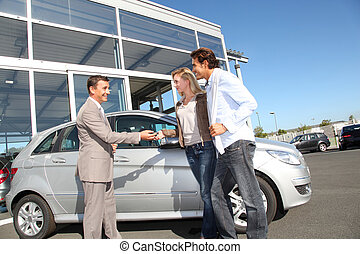 Car seller with couple outside car dealership