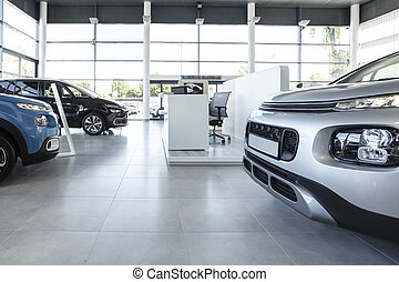 Car seller's station and parked cars in the interior of a modern dealership