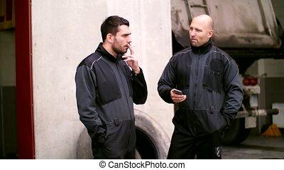 auto mechanics at smoking break talking outdoor - car...