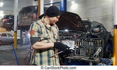 Car service. Brutal mechanic man standing by the car and...