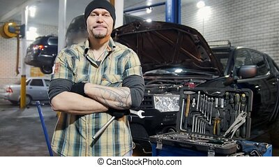 Car service. Brutal mechanic man standing by the car holding...
