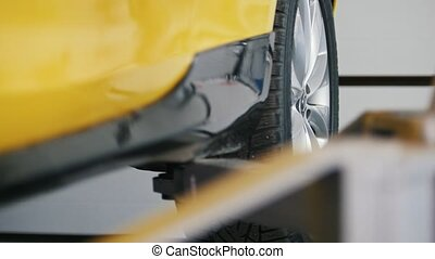 Car service - lifted yellow automobile in garage workshop,...