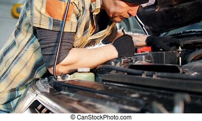 Car service. Mechanic man repairing a car with a wrench