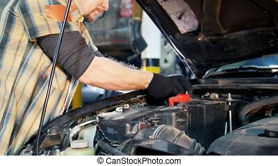Car service. Mechanic man spins the nuts with a wrench
