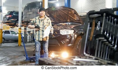 Car service. Mechanic man standing by the car and wipes off the tool
