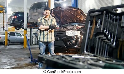 Car service. Mechanic man standing by the car holding a tool and looking in the camera