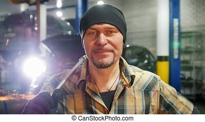Car service. Mechanic man standing by the car