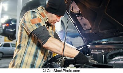 Car service. Mechanic man standing by the car with open hood and repairing car with a wrench