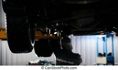 Car service - mechanic unscrewing automobile parts while...