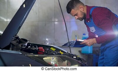 Car service, repair, maintenance and people concept - mechanic checks the quality of the work performed