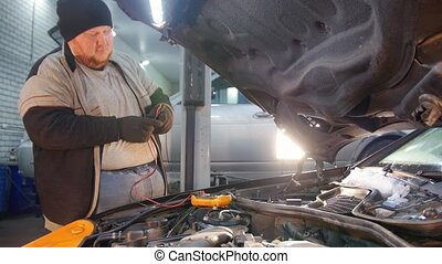 Car service. Thick mechanic man checks the detail