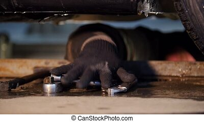 Car service. Thick mechanic man laying under the car and searching for a tool with a hand. Taking a nippers