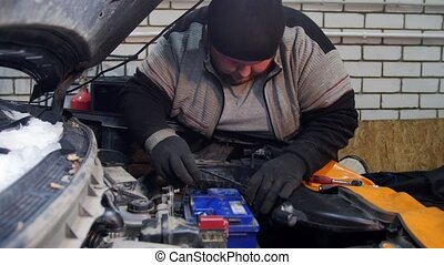 Car service. Thick mechanic man measure the battery
