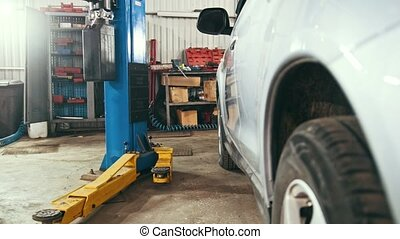 Car service - white vehicle in workshop for repairing or...