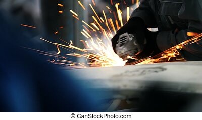 Car service - worker grinding metal construction with a circular saw