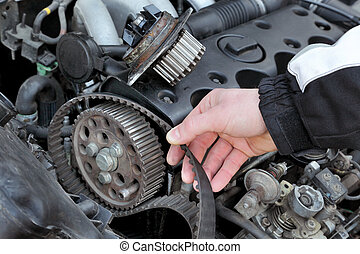 Car servicing - Car mechanic replacing timing belt at...