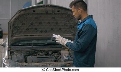 Car servicing, man replacing of paper air filter - Car...