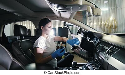 Car servise. A young woman cleansing steering wheel of car....