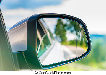 car side mirror with a reflection of the beautiful scenery in it, close-up