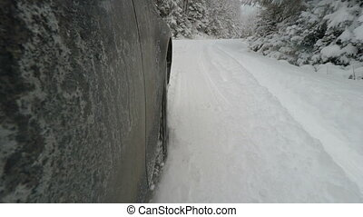 Car skidding in snowy road, side camera view of stucked car