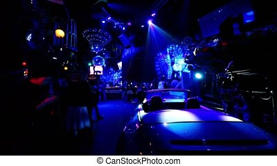 Car standin dark night club with colorful illumination, many...