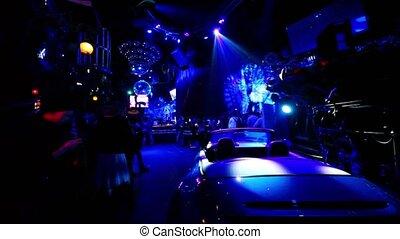 Car standin dark night club with colorful illumination