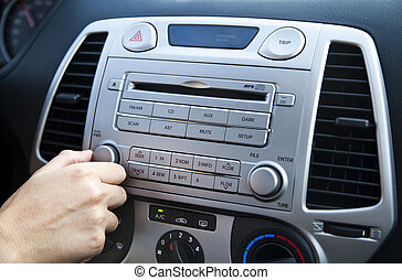 Car Stereo - Adjusting the Volume - The right hand of an...
