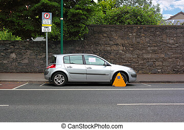 Car street clamped with yellow metal wheel clamp. Trees grow...