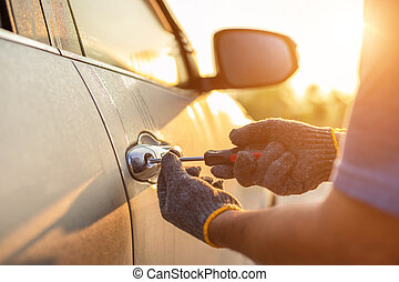 Car technician wearing white gloves and using screwdriver to fix, repair or open the door