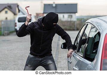 Car thief breaking a glass in car with crowbar