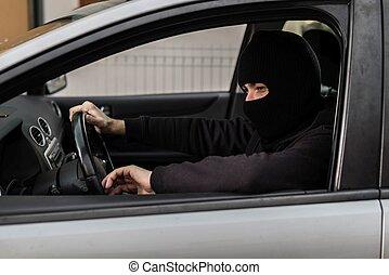 Car thief driving a stolen car.