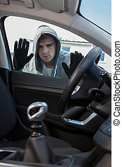 Car Thief Looking Through Window Of Vehicle