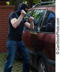 Car thief using crowbar