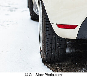 Car tire in winter on the road.