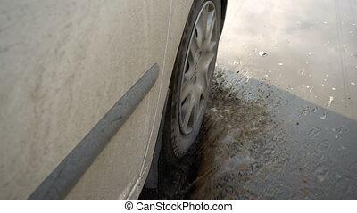 Car tire on a muddy road - Car tire splashing in muddy...