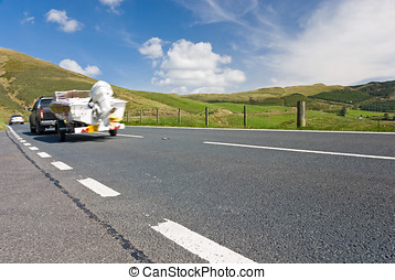 Car towing motor boat on a mountain road in Wales, UK.