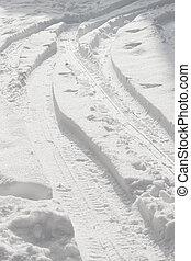 car tracks on fresh snow under the morning light