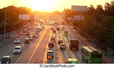 Car traffic against the sunset background.
