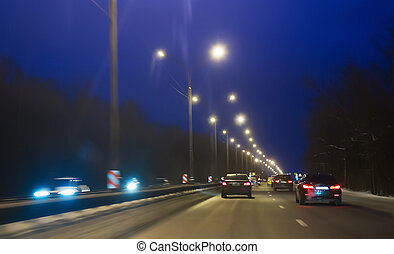 Car traffic in winter on highway at night.