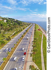 Car traffic on a typical dual carriageway. Aerial view of Sahilyolu Street at Kartal in Istanbul. Showing many cars and coastal street along Marmara Sea. Driving to nature on divided highway in a sunn