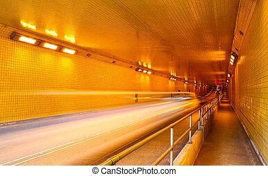 Car trail lights in a tunnel - Blur of a car speeding...