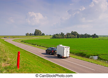 car-trailer traveling on the road to rural areas